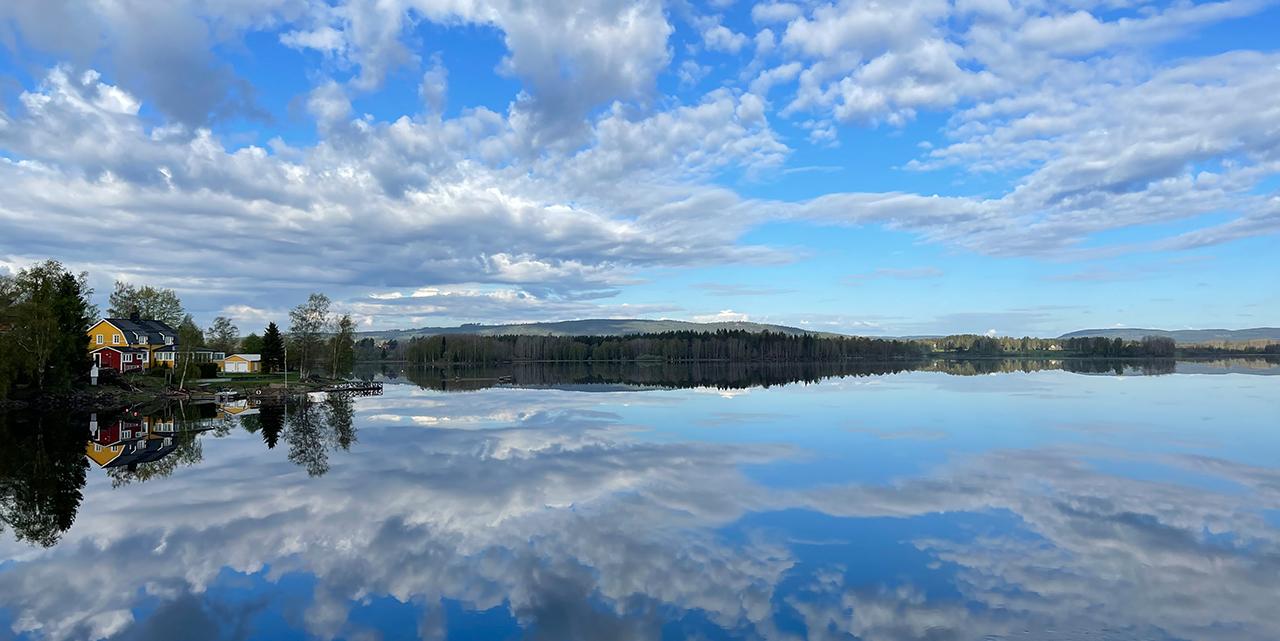 Vy över bysjön med himmel som reflekteras i vattnet